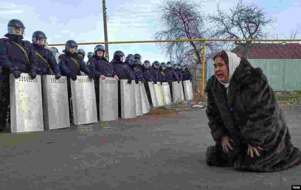 A Romany woman kneels and cries as riot policemen stand in a formation during a protest in the town of Plekhanovo, in the western Russian region of Tula, on March 17. (TASS/Sergei Starikov)