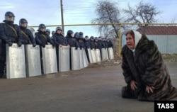 Местная жительница и сотрудники правоохранительных органов во время беспорядков в поселке Плеханово