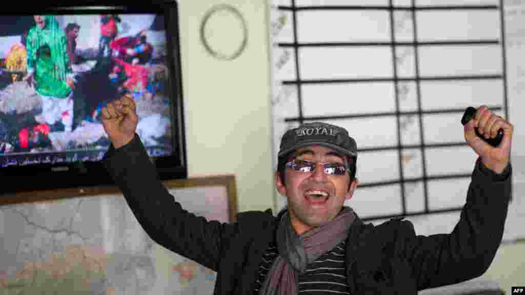 Agence France-Presse (AFP) photographer Massoud Hossaini reacts as the prizewinning photograph is shown on Afghan television on April 17. (AFP/Johannes Eisele)