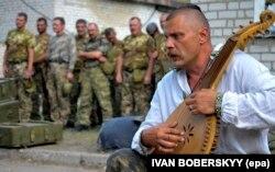 Український воїн грає на бандурі під час прощання із побратимами, які загинули у війні України з Росією. Місто Старобільськ Луганської області, 29 липня 2014 року