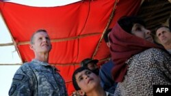 Young Afghan children look on as U.S. General Stanley McChrystal (left) visits a local bazaar at the Baraki Barak district in Logar Province earlier this month.