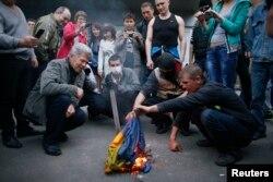 Ресейшілер қарсылық шеруінде Украина туын өртеп жатыр. Донецк, Украина, 4 мамыр 2014 жыл.