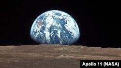 Жердин Айдан чыгышы, Жымжырт деңизи ай көлү (лунное море). Сүрөттү Аполло–11 кемесиндеги астронавт Майкл Коллинз тарткан, 16-июль 1969-ж.