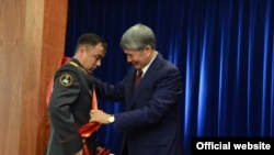 Атамбаев награждает офицера.
