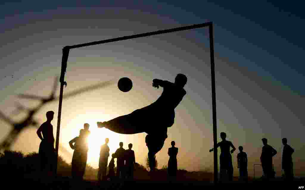 Afghan kids play soccer on a field in Herat Province. (AFP/Aref Karimi)