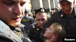 Police detain an opposition protester at a rally in Moscow on May 31