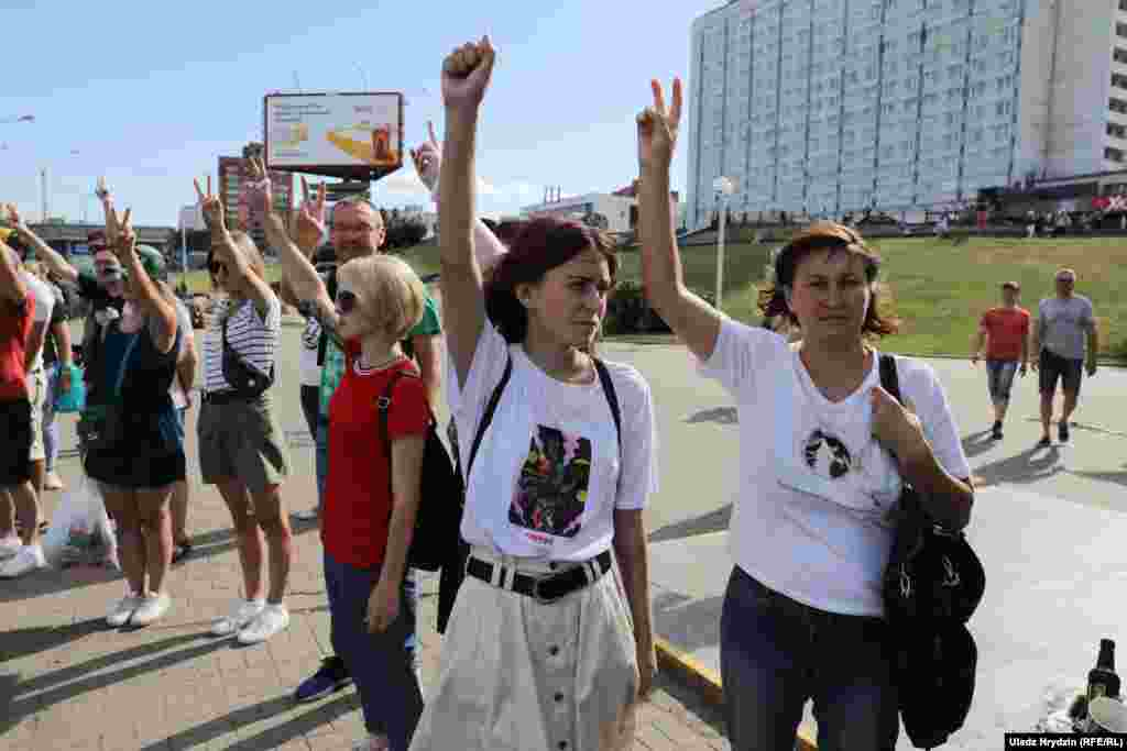 Anti-government protesters show the victory sign in Minsk on August 11.