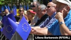 Люди держат флаг Европейского союза в Кишиневе.