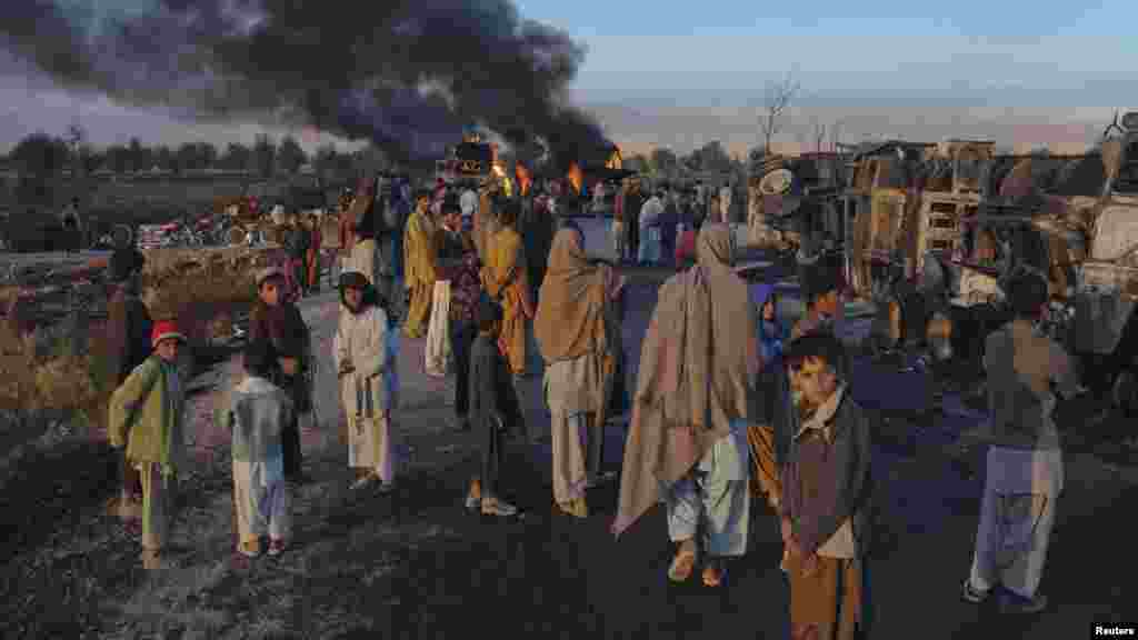 Residents stand near fuel trucks set ablaze in the Bolan district of Balochistan Province in Pakistan in December.