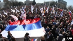 Pro-Russian protesters hold Russian national flags during a rally in the eastern Ukrainian city of Donetsk on April 6.