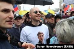 Rapper Oxxxymiron (center) wore a T-shirt in support of Zhukov during a rally in Moscow in August.