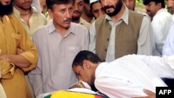 An activist kisses the body of nationalist leader Habib Jalib Baloch, who was shot by gunmen in an attack in Quetta on July 14.