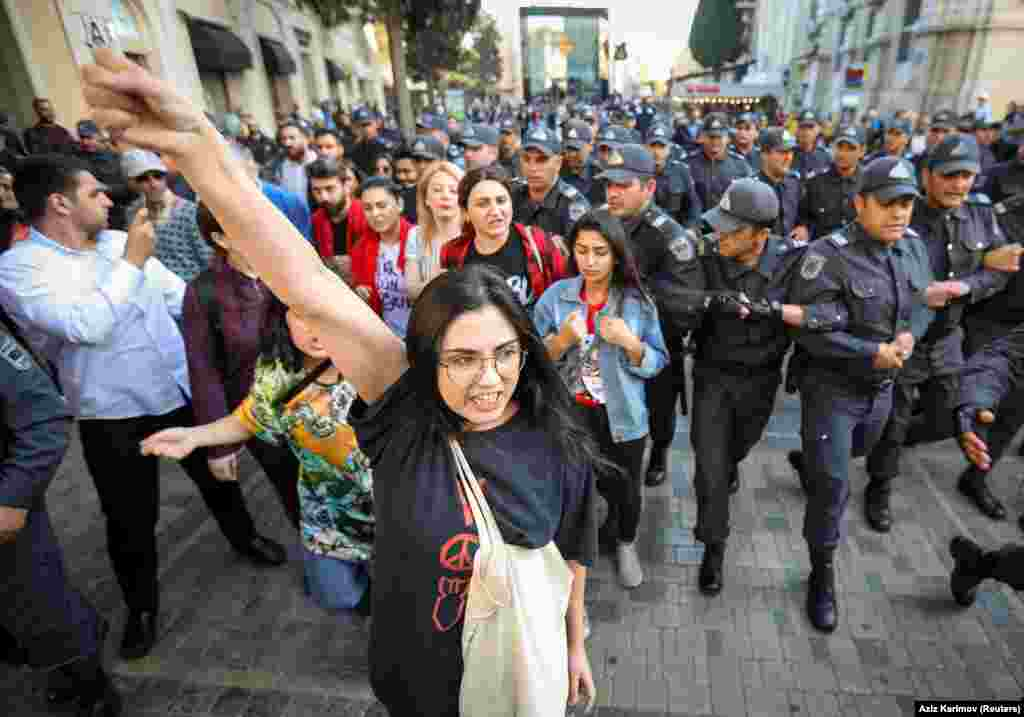 "Police close in on the small group of protesters. A statement by the march organizers said the rally was held for ""the rights of women and young girls who have been deprived of education, married off, coerced, exploited, and committed suicide."""