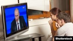 Молодая пара смотрит телевизор, где транслируют выступление президента России Владимира Путина. Улан-Удэ, 20 февраля 2016 года.