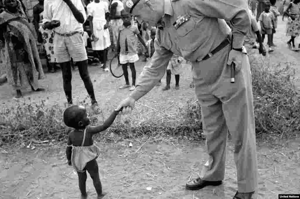 A UN commander in the Congo greets a youngster during his tour of an outpost in 1960. The UN mission there continued until 1964, during which time it evolved from being a peacekeeping presence into a military force.
