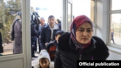 Kazakh citizens are seen crossing the border into their home country from Kyrgyzstan on February 9, 2020.