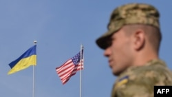 A Ukrainian serviceman stands in front of U.S. and Ukrainian flags during the opening ceremony of the Rapid Trident military exercises near the western Ukrainian town of Yavoriv on September 15.