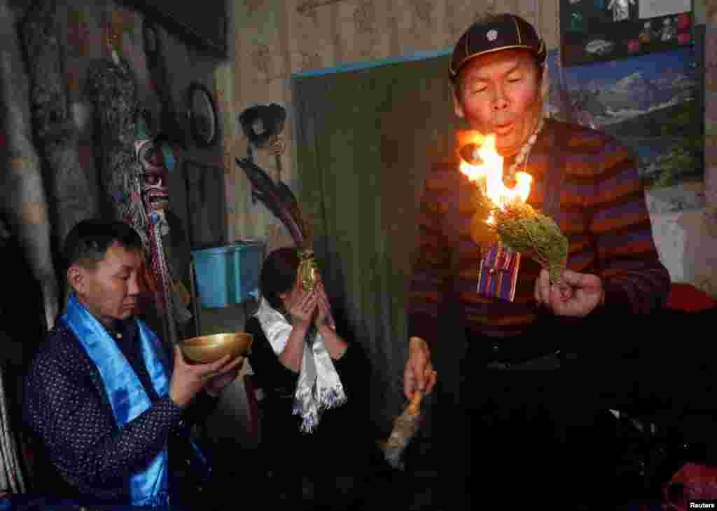 """Вопреки предубеждениям, шаманами могут быть и женщины. На фото: Юрий Ооржак, шаман общества """"Медвежий дух"""", изгоняет злого духа из посетителя."""