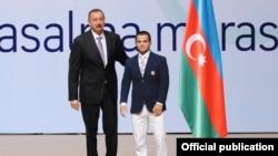 İlham Əliyev XXX Yay Olimpiya Oyunlarında iştirak edəcək güləşçi Rövşən Bayramovla birlikdə