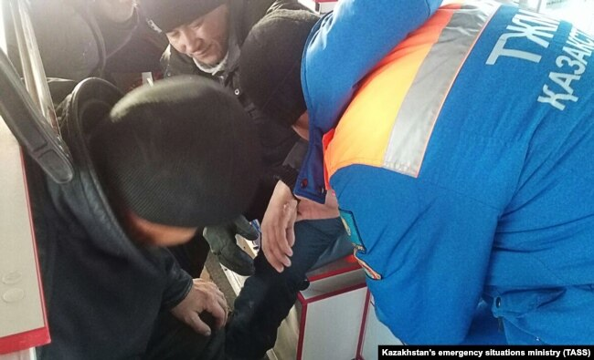 Ёниб кетган автобусдагиларга қутқарувчилар ёрдам кўрсатмоқда. 2018, 18 январь