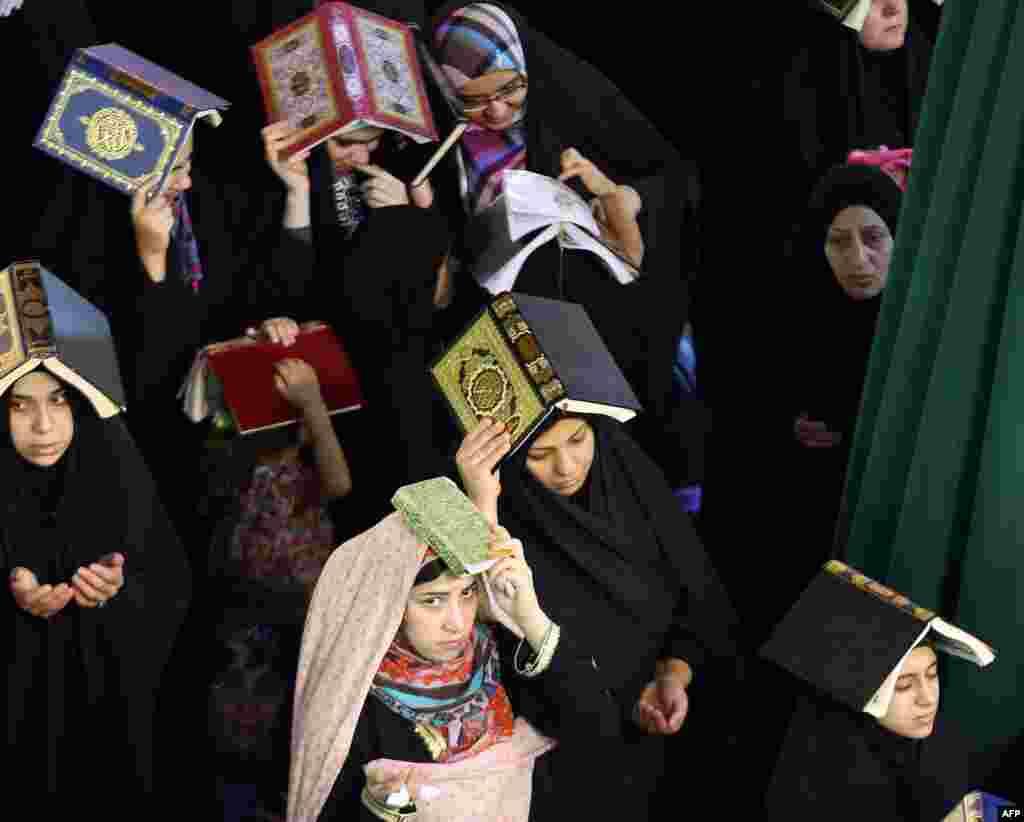 Shi'ite Muslim worshipers place the Koran over their heads as they attend a Lailat al-Qadr (Night of Destiny) prayer in the Imam Musa al-Khadim shrine in Baghdad. (AFP/Ahmad al-Rubaye)