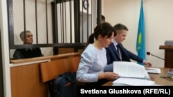Teimur Akhmedov (left), in the defendant's cage, and his lawyers in an Astana courtroom on March 27.