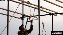 A soldier prepares a noose ahead of a public hanging.