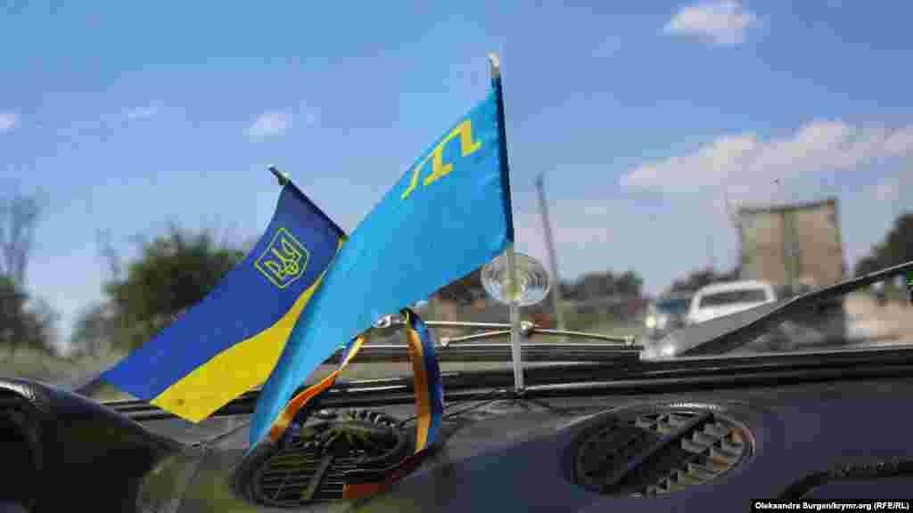 Український і кримськотатарський прапори на лобовому склі в автомобілі Приходька