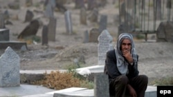 An elderly Afghan man sits at a grave in a graveyard of Afghan casualties of the Soviet war.