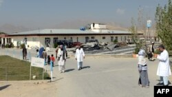 Мужчины и женщины рядом со зданием госпиталя в афганской провинции Вардак. Сентябрь 2013 года. Иллюстративное фото.