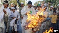 Pakistani protesters burn an effigy of U.S. President Barack Obama as they protest against Facebook in Lahore on May 26.