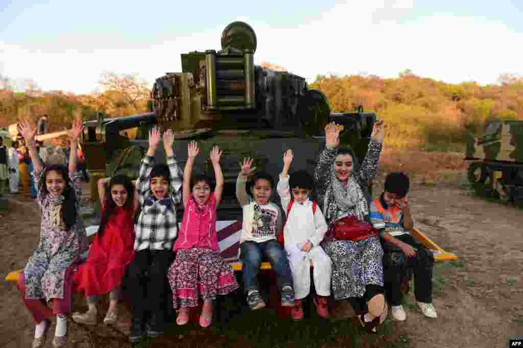 Pakistani children sit on a tank as they enjoy a public holiday ahead of the National Day celebration in Rawalpindi. (AFP/Farooq Naeem)