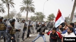 Riot policemen disperse protesters during a demonstration in Basra on March 4.