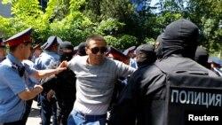 Қазақстандағы наразылық шарасына қатысушыны ұстап жатқан полиция. Көрнекі сурет