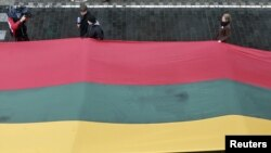 Lithuania -- People carry about 200 meter long sash in Lithuanian flag colours during Day of the Defenders of Freedom celebration in Vilnius, 13Jan2011