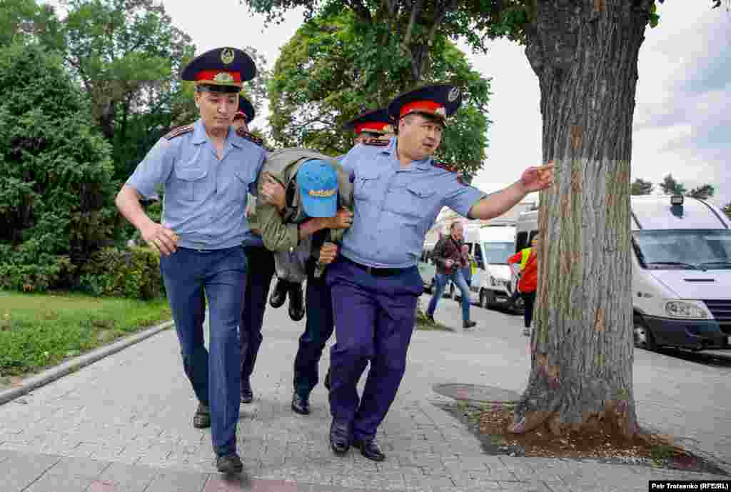 Police detain a man in the center of Almaty, Kazakhstan, before an illegal rally on June 10. Find out more details on how police detained bystanders in 'I Was Just Passing By!': A Second Day Of Detentions In Almaty. (Petr Trotsenko, RFE/RL)