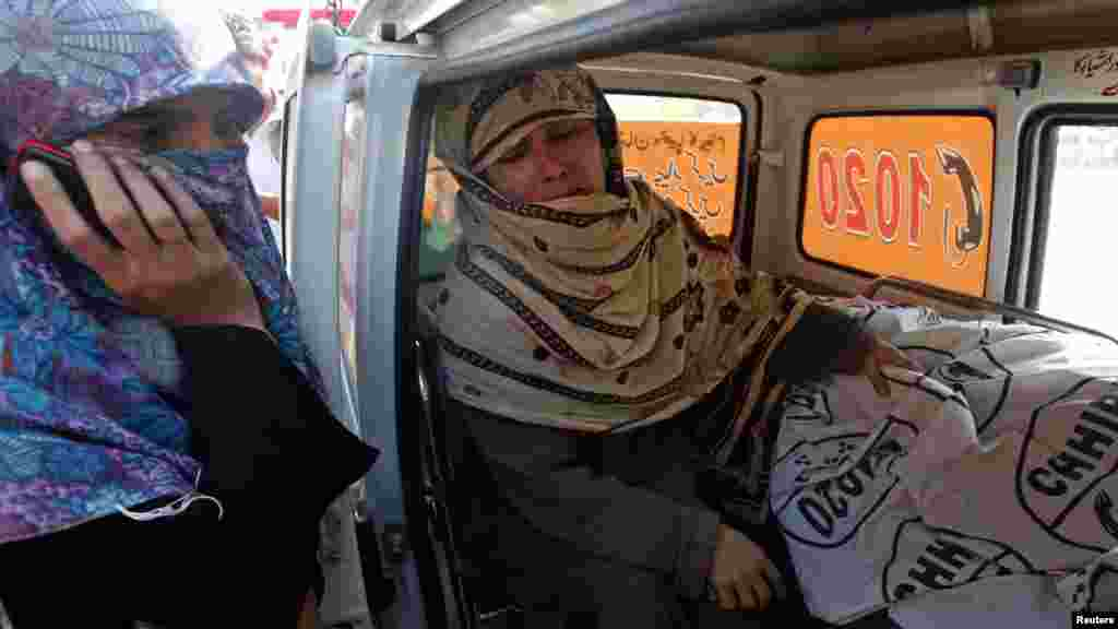 Rukhsana Bibi weeps next to the body of her daughter Madiha, a slain polio-eradication worker, in an ambulance outside Jinnah Hospital in Karachi on December 18. (Reuters/Akhtar Soomro)
