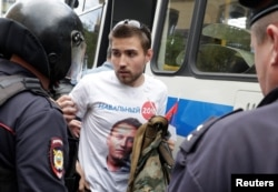 Riot police detain a man dressed in a T-shirt depicting opposition leader Aleksei Navalny during an anticorruption protest in central Moscow on June 12.