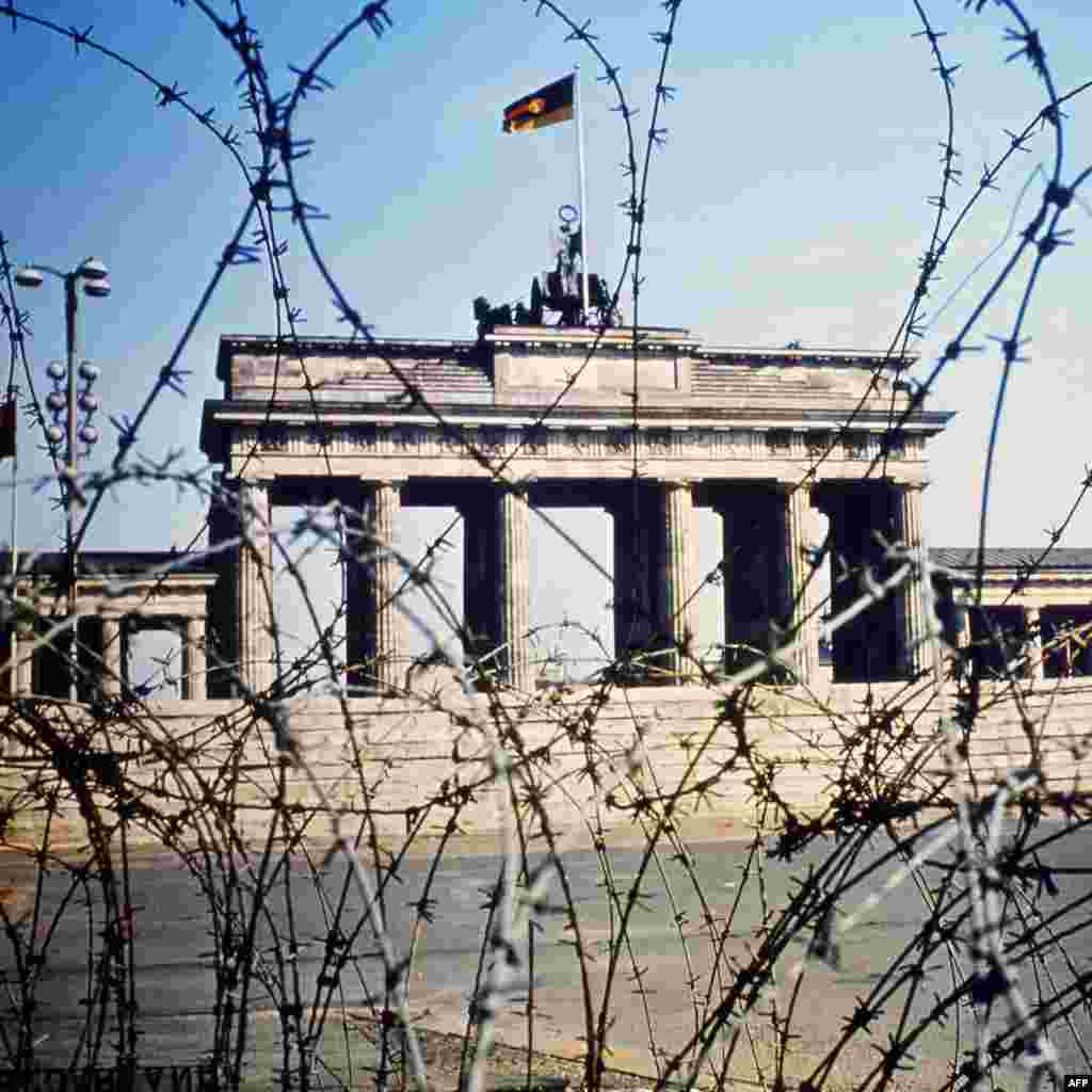 The Brandenburg Gate is seen through a barbed wire fence in June 1968.