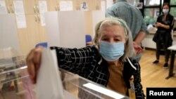 O alegătoare purtând mască votează în cadrul alegerilor naționale, la o secție de votare din Belgrad.