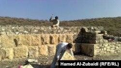 عمال بناء يشاركون في عمليات صيانة سور نينوى التاريخي