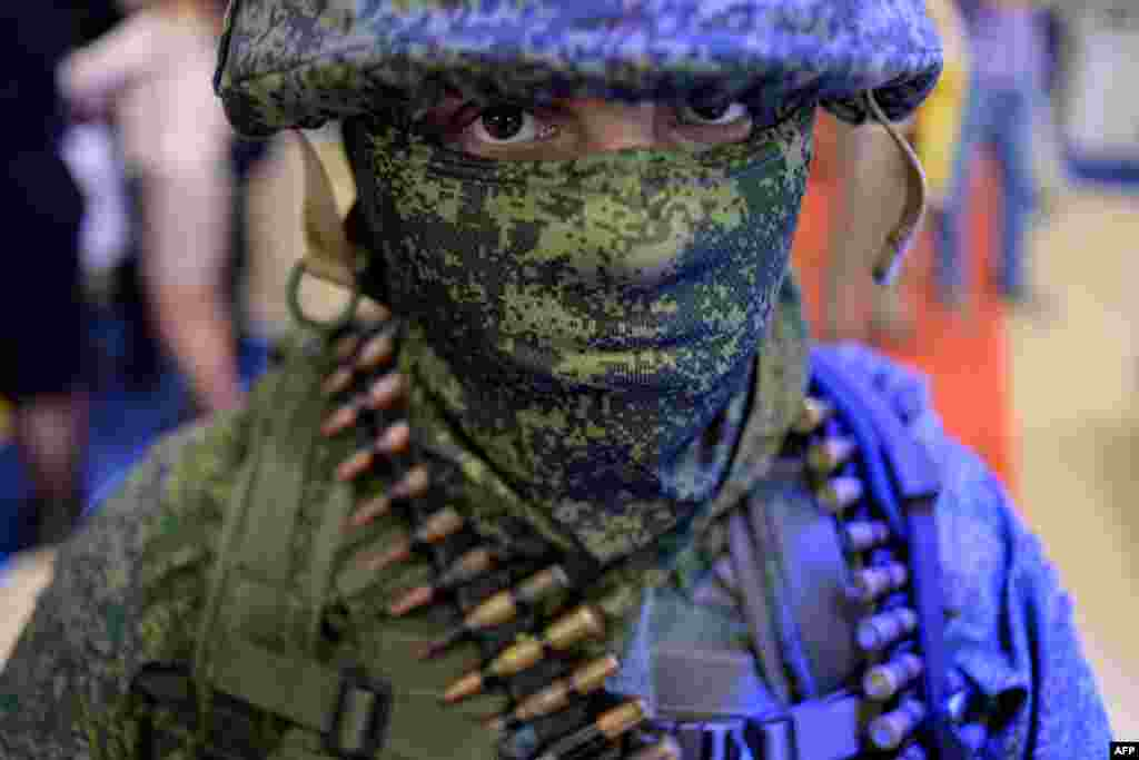 A participant poses for a photo during the Interpolitex-2015 exhibition of police and military equipment in Moscow on October 22. (AFP/Kirill Kudryavtsev)
