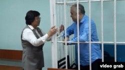 Бывший президент Кыргызстана Роза Отунбаева разговаривает в зале суда с арестованным оппозиционным политиком Омурбеком Текебаевым. Бишкек, 22 июня 2017 года
