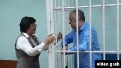 Қырғызстан экс-президенті Роза Отунбаева (сол жақта) қамауда отырған оппозициялық саясаткер Омурбек Текебаевпен сот залында сөйлесіп тұр. Бішкек, 22 маусым 2017 жыл.