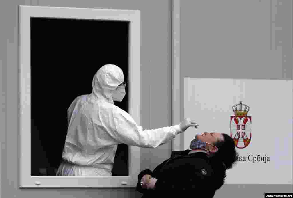 Сербский медицинский работник берет мазок у женщины во время теста на коронавирус в Белграде. (AP/Дарко Воянович)