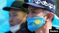 Мужчина в защитной маске с флагом Казахстана на митинге оппозиции в Алматы. Казахстан, 27 марта 2021 года.