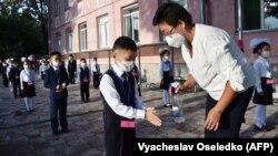 Учитель обрабатывает санитайзером руки первоклассников. 1 сентября 2020 года.