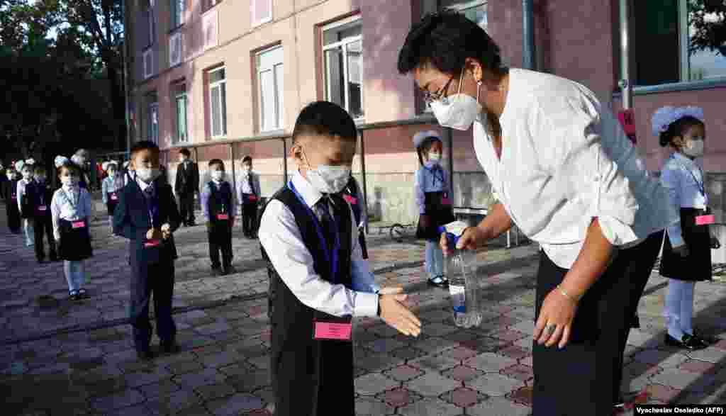 Киргизстан. Вчителька дезінфікує руки киргизьких школярів у перший день занять у Бішкеку 1 вересня