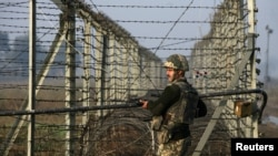 An Indian border guard patrols near the fenced frontier with Pakistan along the Line of Control in Kashmir (file photo).