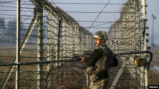 An Indian Border Security Force (BSF) soldier patrols near the fenced border with Pakistan in Jammu and Kashmir state.